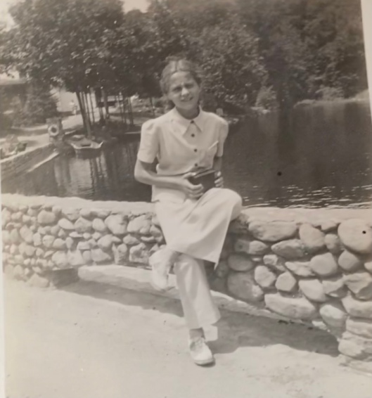 black and white photo of girl on stone bridge